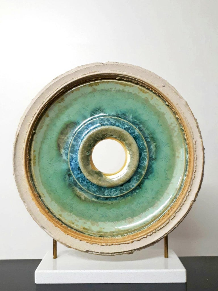 This beautiful, contemporary circular sculpture made from ceramics with crystal glaze and 24k gold leaf stands on an elegant white granite base. It is a timeless piece full of detail from the burning and glazing process. Titled on verso.  About the