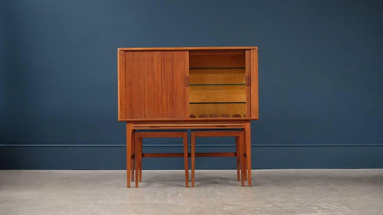Amazing bar cabinet in beautiful patinated teak with reeded tambour doors and two occasional tables designed by Kurt Ostervig for KP Mobler, Denmark. Rare and fantastic piece with great proportions.