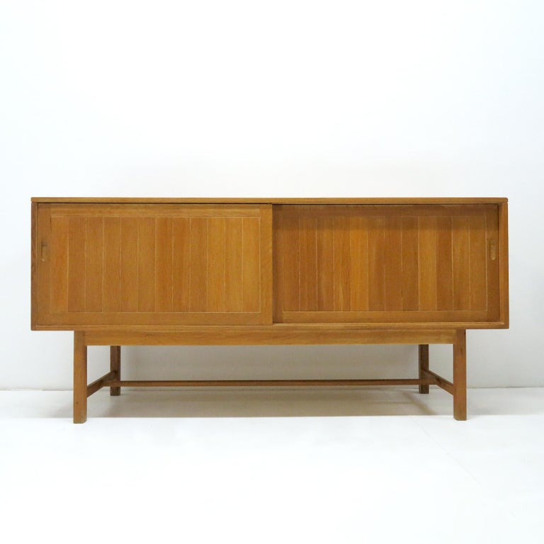 Bold Danish modern, solid oak credenza by Kurt Ostervig for KP Möbler, 1960, with two sliding doors, one center shelf behind one door and one center shelf and four felt lined drawers behind the other door, all in sturdy oak in great condition.