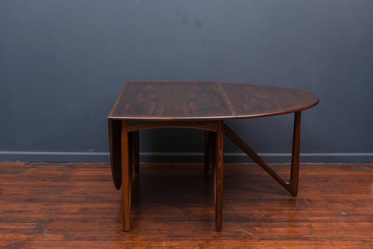 This spectacular rosewood dining table was designed by Niels Koefoed for Koefoeds Hornslet in 1964 (frequently mis-attributed as Kurt Østervig for Jason Møbler) and features an oval top over folding V-legs. The drop leaves move up and down on