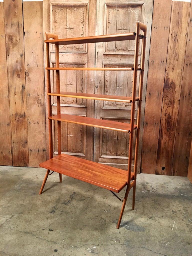 Modular and adjustable Danish modern teak wood bookshelf or room divider with brass support structure.