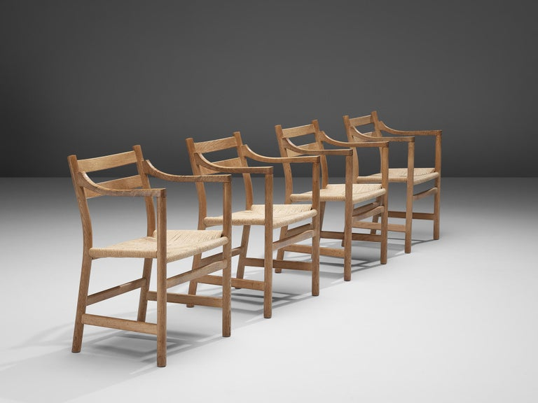 Kurt Ostervig for KP Møbler, four chairs model KP22, oak and papercord, Denmark, 1960s  This set of four armchairs is designed by Kurt Ostervig and produced by KP Møbler in the 1960s. This dining set is modest, well executed and quintessentially