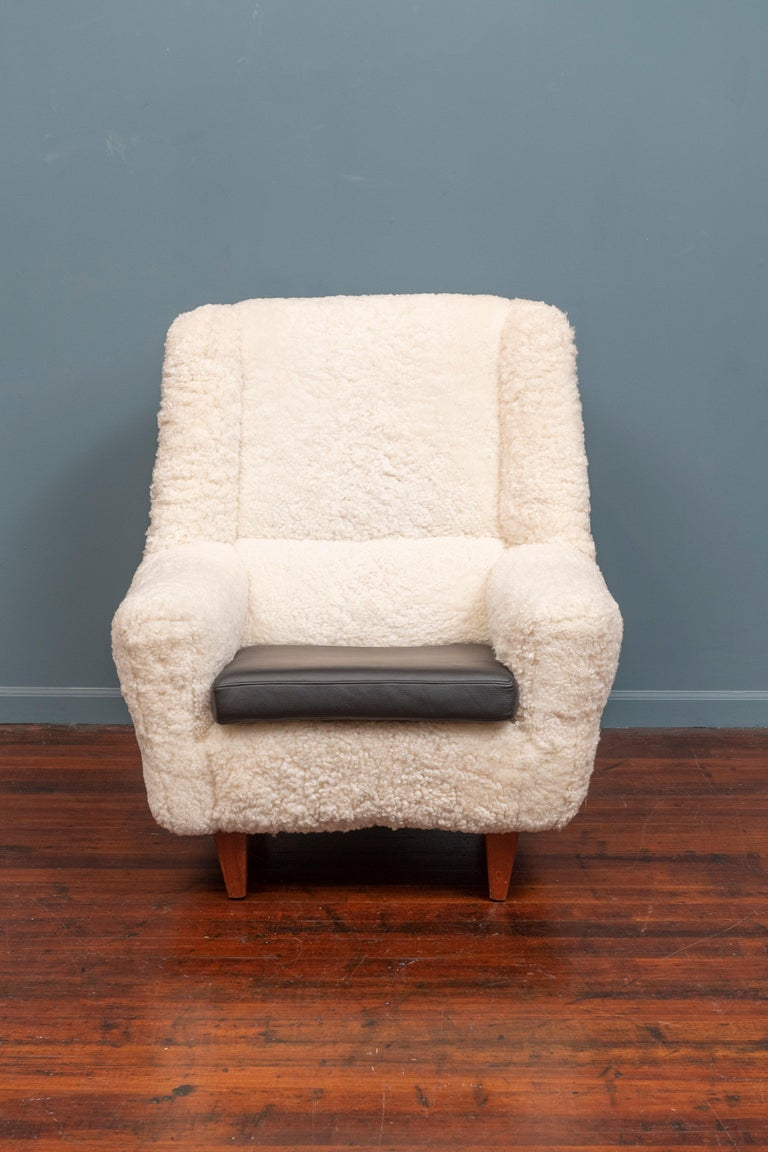 Kurt Ostervig design lounge chair, model 61. Newly upholstered in fluffy inviting lambswool with a new black leather cushion, ready to enjoy.