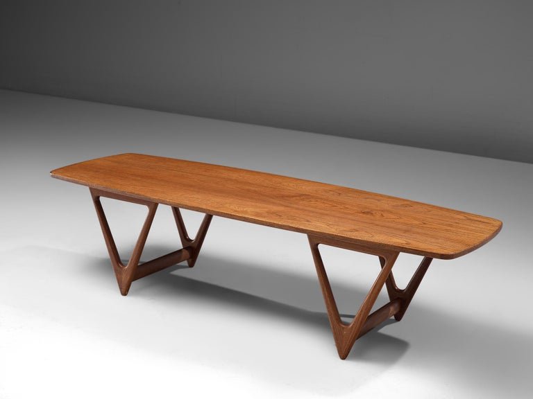 KurtØstervig, 'Surfboard' coffee table, teak, Denmark, 1950s.  Boat-shaped coffee table with a long tabletop with sweeping teak veneer and beautifully sculpted V-shaped legs. A design by the Dane Kurt Østervig from the 1950s. The low table