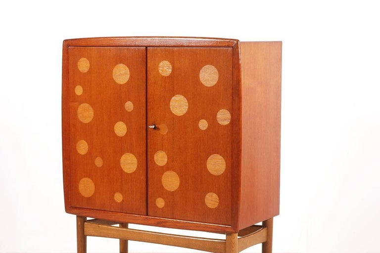 Here is a rare bar cabinet designed by Kurt Østervig and manufactured by K.P. Møbler in the 1940s.  Teak cabinet with oak inlays and base. The interior is composed of two birch drawers and tablet. The shelves are in glass and the bottom in several