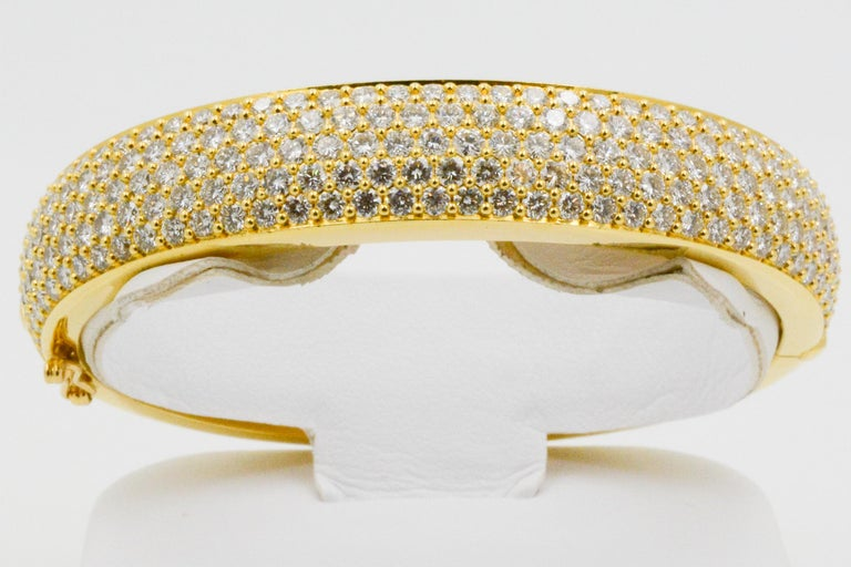 This 18k yellow gold Kurt Wayne bangle features a panel of rows of 193 round brilliant pave diamonds, weighing a total of approximately 10 carats. Glamorous and enchanting is this 10.00 carat round brilliant pave diamond bangle. With a tongue &