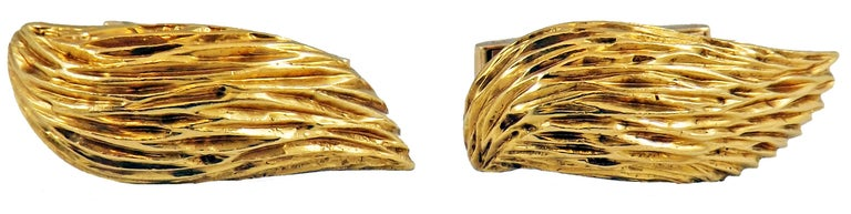 Beautifully handcrafted and wonderfully designed cuff-links by renown London jeweler Kutchinsky. 18 karat yellow gold hand crafted wing shaped cuff-links with beautiful hand-engraved surface. A unique and bold look on every cuff.   - 1 1/8 inches