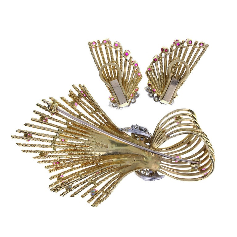 18 carat yellow gold wires twisted to form a spray brooch and matching pair of earrings. Set with round brilliant-cut diamonds on a central white gold wrap on the brooch, with randomly placed, round-cut rubies. Earrings set with a border of diamonds
