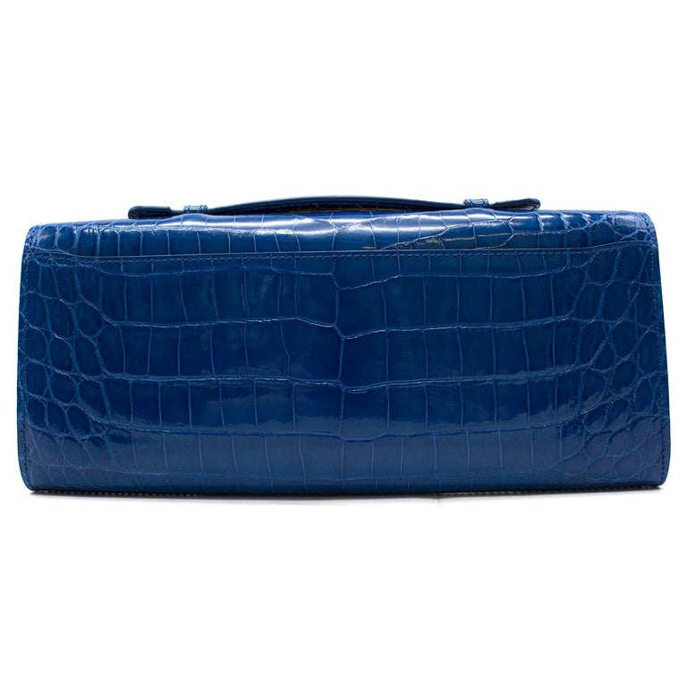 Kwanpen Tanzanite Croc Leather Raffles 1819 Clutch  - Current from The Raffles Collection  - Structured lines with iconic Raffles hardware, gold toned  - Carried by top handle or shoulder chain strap. - Internal features: 1 Large Compartment; 1