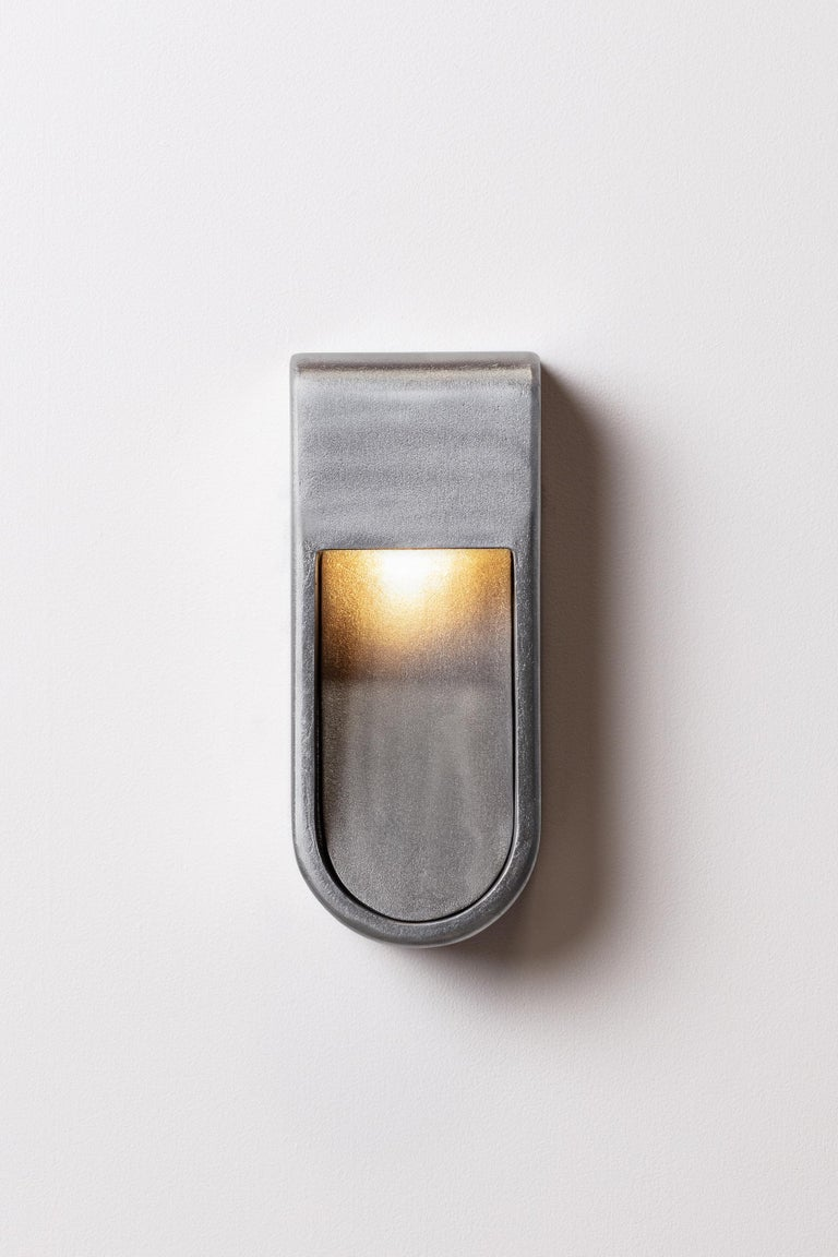 Kyotois a unique outdoor/indoor lamp collection. Sand cast in aluminum with a raw aluminum finish but available blackened, brass, bronze and silver. The sconces are handmade sculptures that are resistant to the elements.  Each piece is