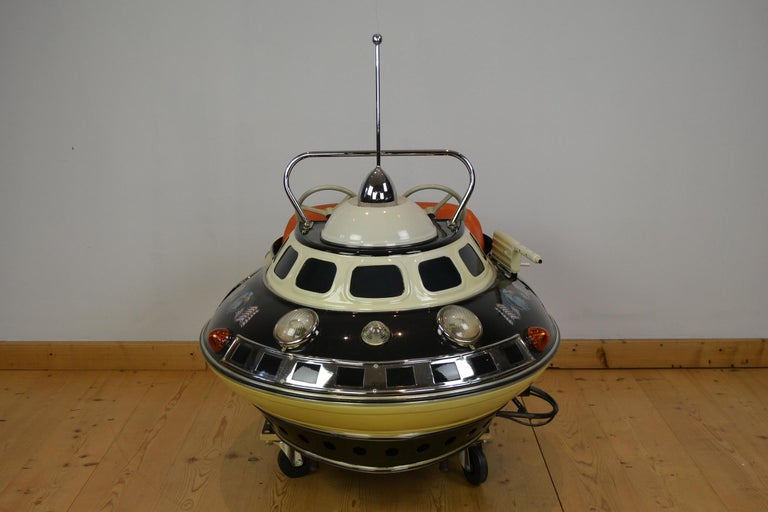 Space Age carnival ride seat in the shape of an UFO, made by L' Autopede Belgium. This handmade metal 2-seat carousel ride object is in science fiction style and an awesome piece of carnival art. An astronautics shuttle for 2 children, still