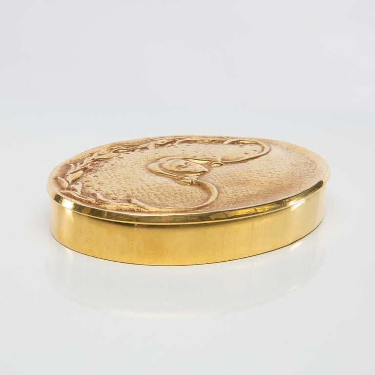 This charming gilded bronze compact represents a girl with braids giving form to a halo.    Manufactured around 1950, the object is in very good condition and has a natural patina. It also has its original mirror and sieve.  It is signed with a