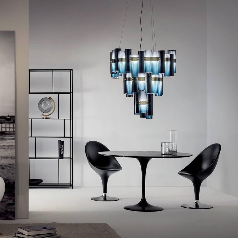 Designed by Lorenza Bozzoli and part of the La Lollo collection. The several cylinders forming this piece have a blue-tinted finish and evoke the glamour of the 1950s. This lamp is entirely made of durable and completely recyclable engineered