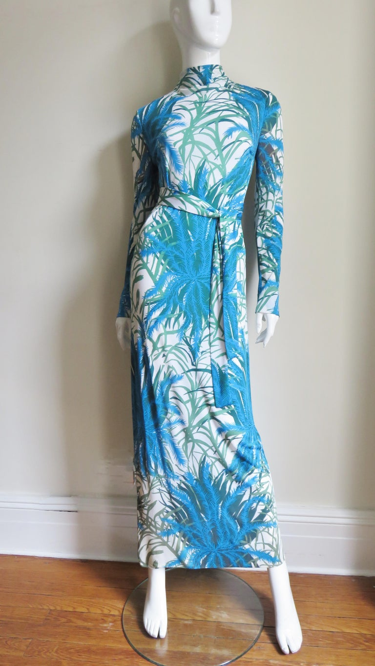 A maxi dress and over skirt in fine silk knit in a beautiful pattern of ferns and leaves in shades of green and blue on a white background from La Mendola. The dress is a long sheath with a stand up collar closing in the back with 3 dozen small self