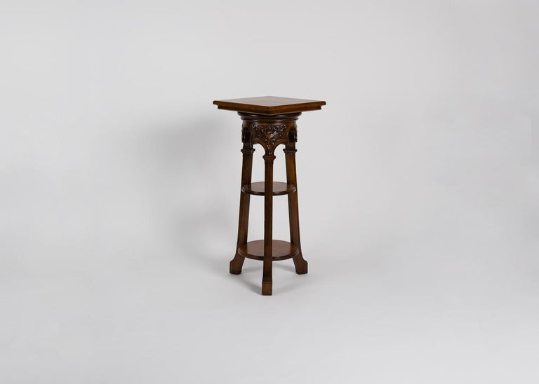 This Art Nouveau tripodal pedestal features intricate relief carvings near the top, as well as a pleasant juxtaposition between the square surface and round lower shelves.