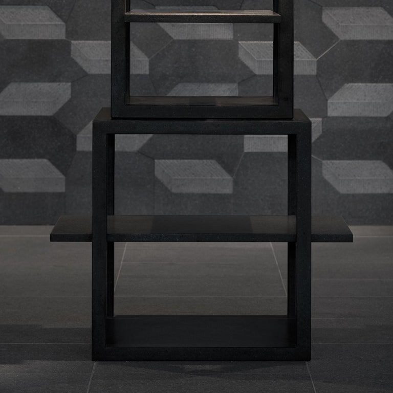 This contemporary bookshelf is entirely made of lava stone, fashioned by stacking four increasingly small and concentric hollow cubic shelves one on top of another. The trampolines protrude on horizontal axes, providing precious display surface. The