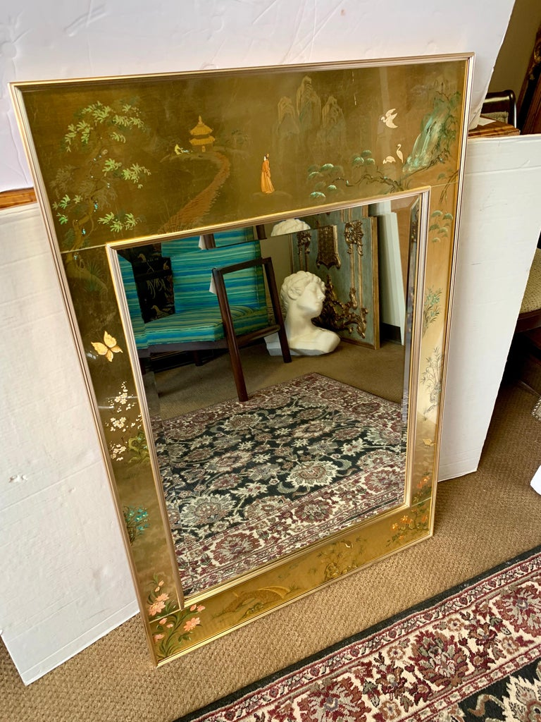 Midcentury Classic chinoiserie reverse hand painted and gold leaf framed beveled mirror with signature on bottom right. A brass frame surrounds the beveled mirror and the decorative band. Great detail, scale and size.