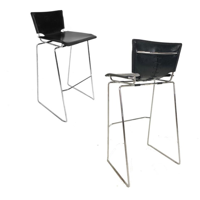 Incredible set of 6 durable and stackable counter height stools by ICF. Designed by Toyoda Hiroyuki. Thick tanned black leather covering a heavily chromed base. Wonderful details of stitched and laced leather. Perfect for home or commercial use with