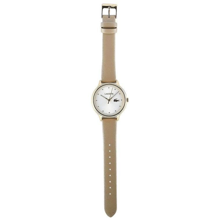 This is the Lacoste Constance watch, reference number 2001007. It is presented with a gold-tone stainless steel case that measures 38 mm in diameter. The case is water-resistant to 30 meters and mounted onto a pearly beige leather strap, secured on