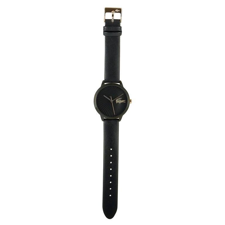 This is the Lacoste Lexi watch, reference number 2001069. It boasts a 38 mm stainless steel case that is presented on a black leather strap, secured on the wrist with a tang buckle. The case is water-resistant to 30 meters. The black dial boasts a
