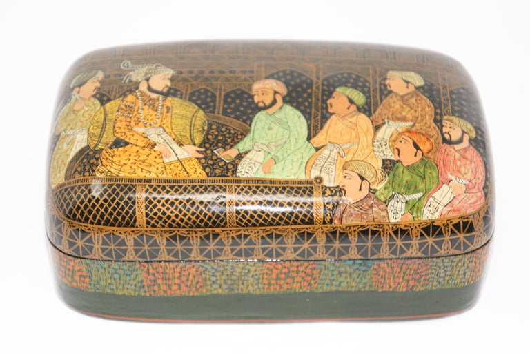 Hand painted miniature lacquer papier mâché box in rectangular shape with lid. Decorated with a figural 17th century scene and floral designs on sides on black background. Kashmiri box miniature hand painted with Mughals Maharajas wearing 17th