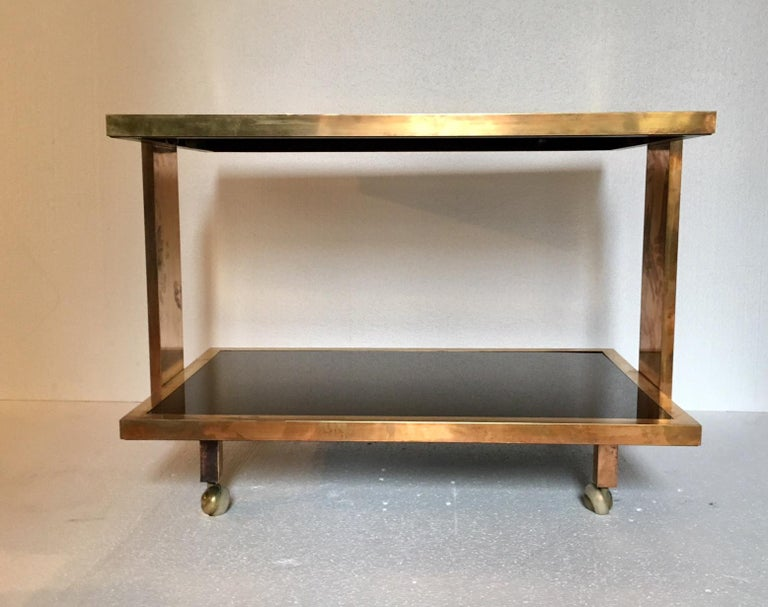 Elegant bar cart made of gold brass and lacquered wood in maroon, with two shelves, J.C. Mahey style.