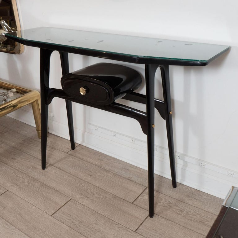 Lacquered dark wood console with unusual oval form drawer.