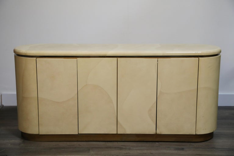 A lovely lacquered goatskin sideboard or credenza, with beautiful grain detail in the goatskin hides, in the style of Karl Springer and Steve Chase, circa 1970s. With a finished back it can also be used as a room divider.   Four doors open to