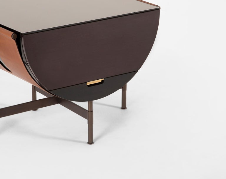A hammock-like wide leather strap supports a half circle form and is lacquered black. The leather straps are wrapped around T-shaped steel arms. A brass arm extends to support the cabinet door when open. The Packsaddle Side Table is accompanied with