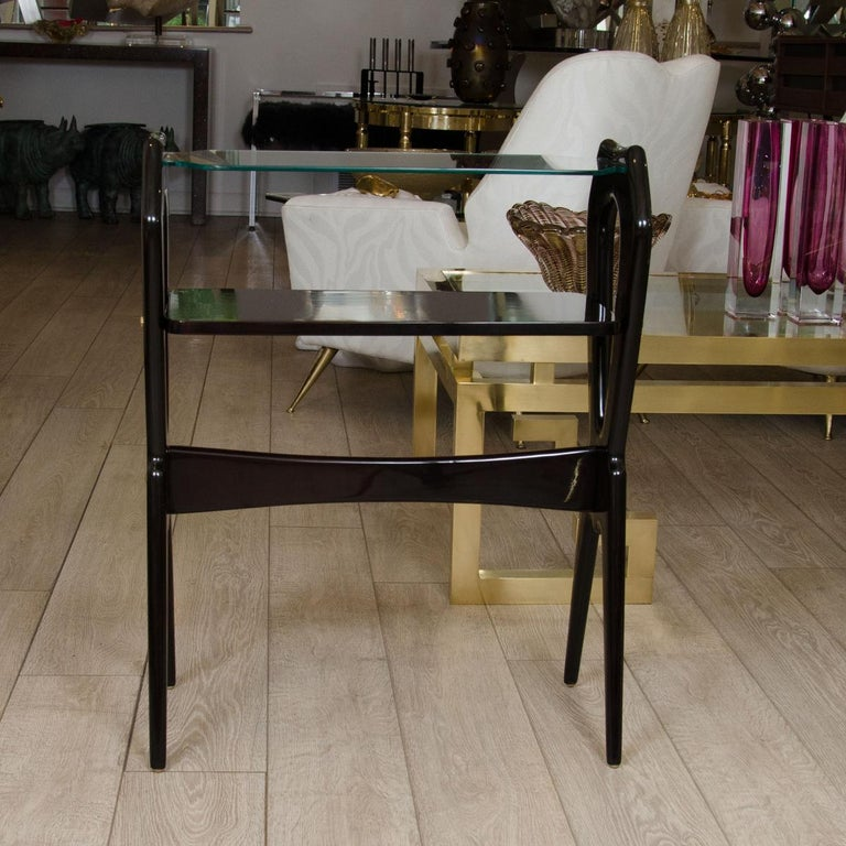 Lacquered wood and glass top end table with brass detail.