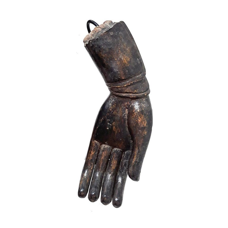 A wooden sculpture of a Buddha hand in a traditional gesture known as Verada Mudra, meaning Compassion / Sincerity, early 20th century.  Once part of a large Buddha sculpture, this fragment was reclaimed and mounted on a black metal stand as a
