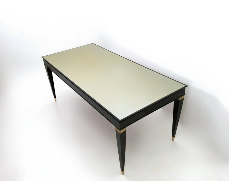 1950s. This table is made in black lacquered wood and features brass feet caps and details and a taupe back-painted glass top. It is a vintage item, therefore it might show slight traces of use, but it can be considered as in excellent original