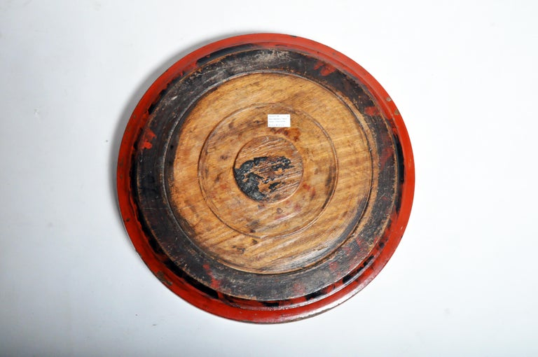 This large wooden tray was carved from a single piece of teak wood and covered in multiple layers of natural tree sap lacquer. Black lacquer was used to fill in the pores of the wood and build up a thick, protective surface. Red cinnabar lacquer