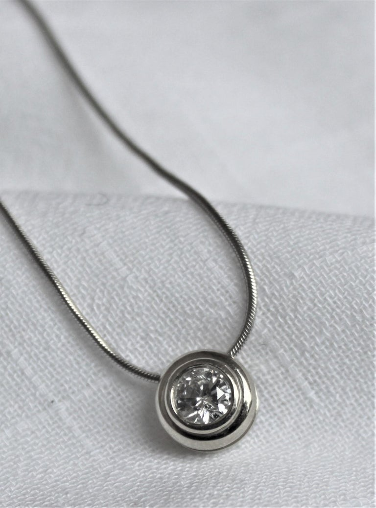 This ladies 14-karat white gold and brilliant cut bezel set diamond pendant was made presumably in the 1970s in the midcentury Modernist style and most likely originates from the United States. The snake link chain is also 14-karat white gold and is