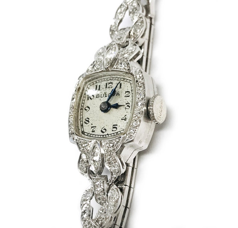 Vintage Art Deco Bulova Platinum Diamond Bracelet Watch, Circa 1930s. The dial is framed in round diamonds with black hour and minute hands. The watch features fourteen 1.3mm round melee diamonds, thirty-two 1.7mm round melee diamonds, thirty-one