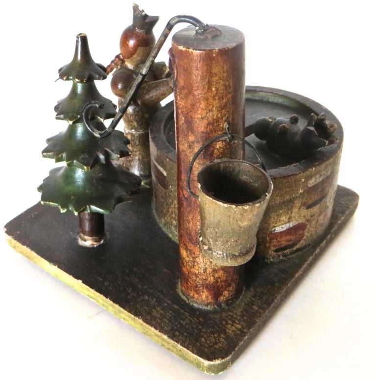 Very interesting wooden still bank with lots going on. All hand-carved of wood with four small circular risers elevating the base. There is a water pump with a bucket hanging from it and a metal pumper attached to the top. A hand-carved and painted
