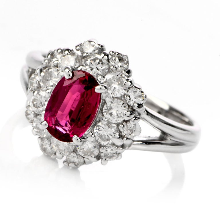 This beautiful ruby and diamond ring is crafted in solid platinum, weighing 6.5 grams and measuring 12mm x 6mm high. Centered with one oval shaped prong-set ruby, weighing approximately 0.96 carats. Further accented by a clustered halo of 22