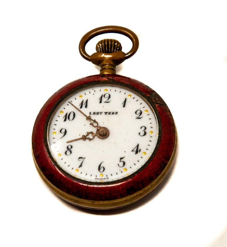 Offering this sweet little ladies pocket watch. Marked Lady Tess on the face of the watch and on the bottom marked Swiss. Having red enamel around the face and over the back of the brass body.