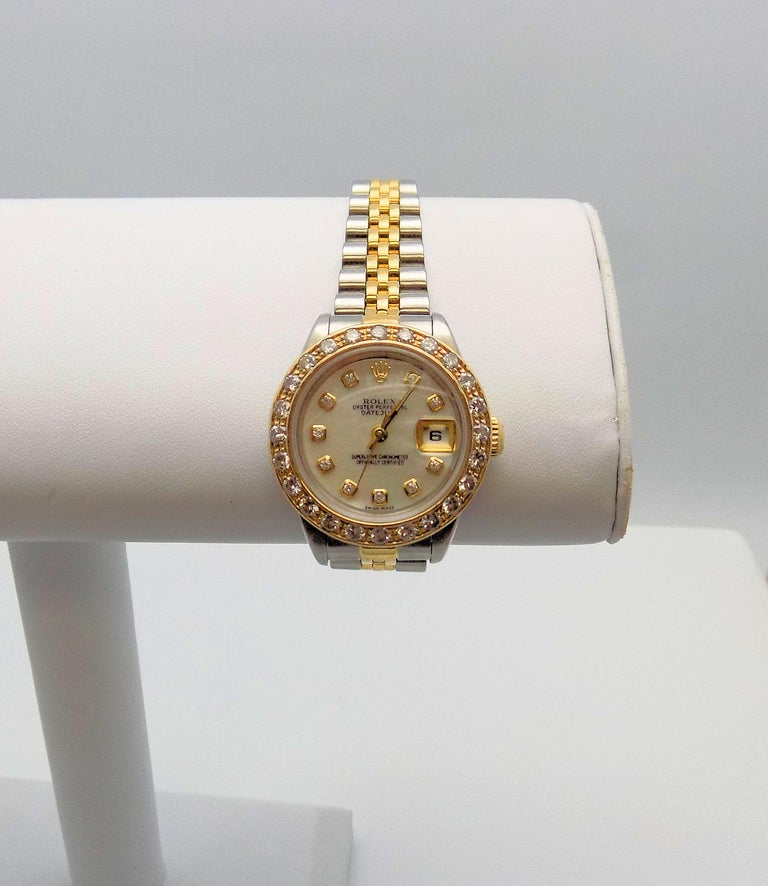 Classic 18 Karat Yellow Gold and Stainless Steel Lady's Wrist Watch by Rolex featuring Oyster Perpetual Date Just Mother of Pearl Dial, 10 Round Brilliant Diamonds, (After Market Bezel) 24 Round Brilliant Diamonds 1.25 Carat Total Weight, SI, H, 1