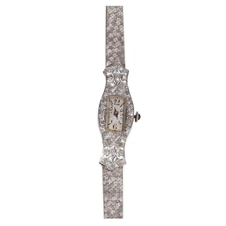 The rectangular dial with Arabic numbers and arrow hour markers to a broad brilliant-cut diamond bezel, cabochon sapphire-set winding crown, white gold bracelet, mechanical movement.  Offered with 1 year warranty accurate timekeeping.
