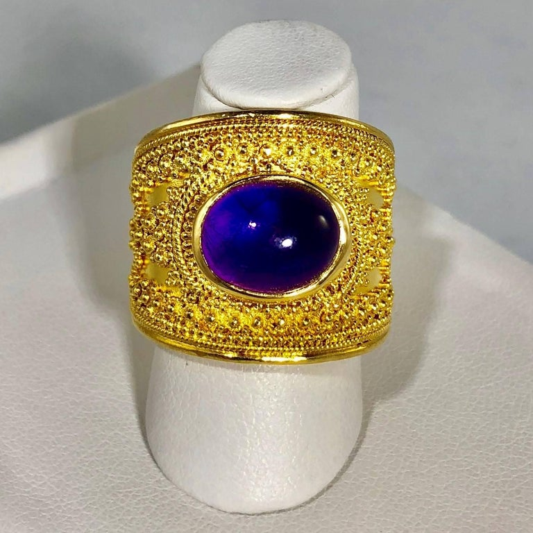 Lalaounis 18 karat Cabochon Amethyst vintage cocktail ring. This stunning piece is a Llias Lalaouis original created in Etruscan style, 18 karat yellow gold- weight 19.8 grams, 12.8 Dwt.. The center stone is a Cabochon cut Amethyst, approx. 2.5