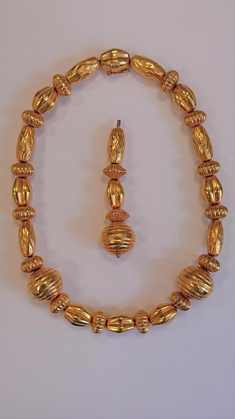 A Lalaounis 22 Carat Yellow Gold Minoan Bead Pendant Necklace. Circa 1970s. The 22ct hammered yellow gold necklace featuring different sizes and shapes of beads with a removable drop in the centre. All held together with beautiful and intricate 22ct