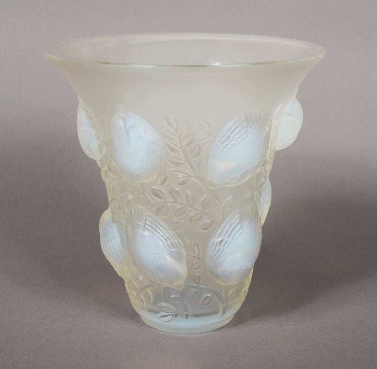 Saint Francois opalescent vase designed by René Lalique, circa 1930. This example dates to circa 1945 just before production ended for this design. The vase is decorated with chubby sparrows on branches. There is a small nick to the side of the rim