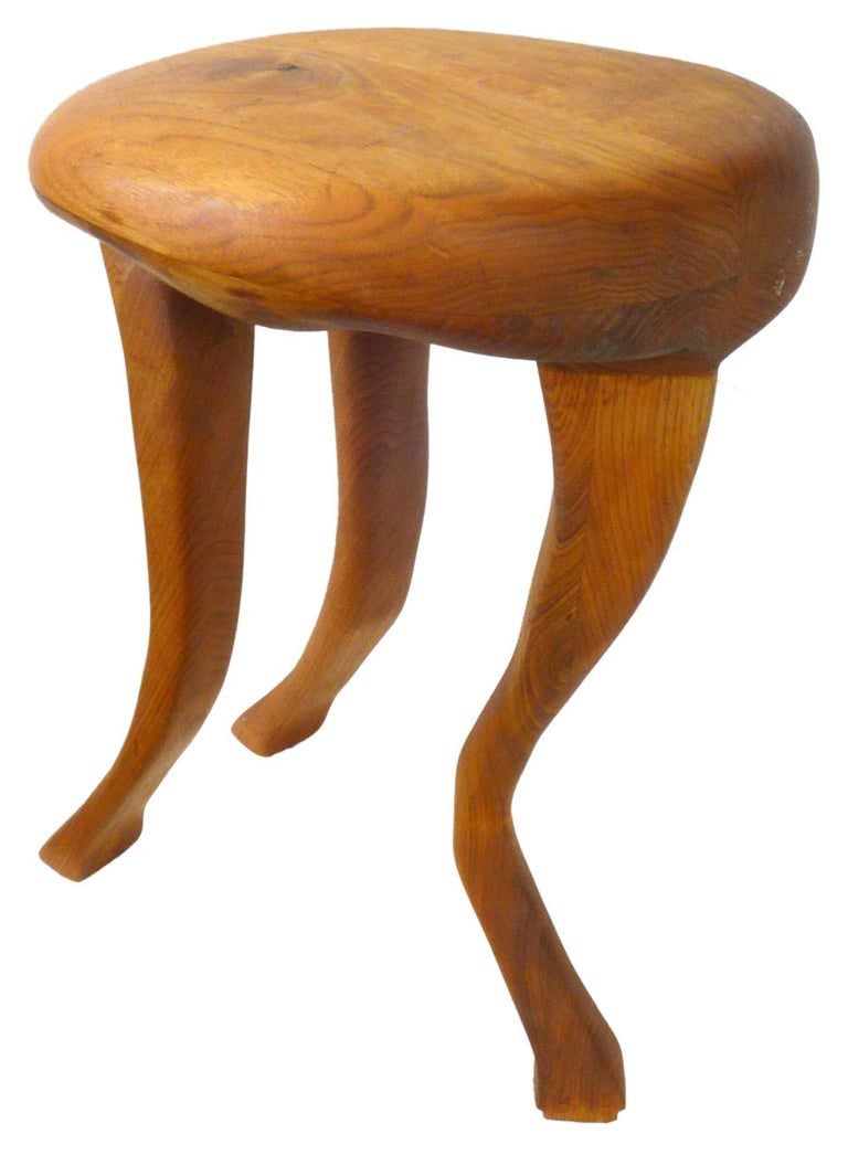 A fantastic hand carved laminated wood stool. An alluring and unusual 3-legged form of clear zoomorphic intent with stylized mammalian legs seemingly ready to pounce. Wonderful from all angles with great, subtle detail throughout. Unexpected and
