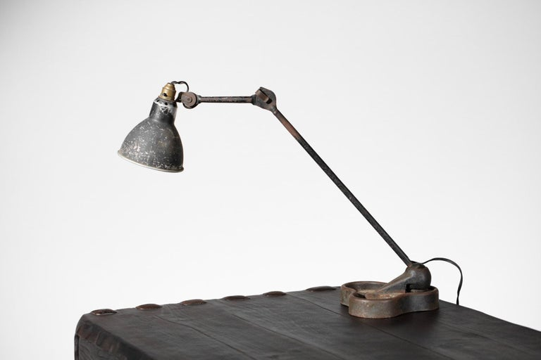 Desk lamp by French designer Bernard Albin Gras from the 1950s. Steel structure mounted on a cast iron base and perforated steel shade. Nice patina (cf photos). Industrial style lamp that can be found in many of Le Corbusier's projects.