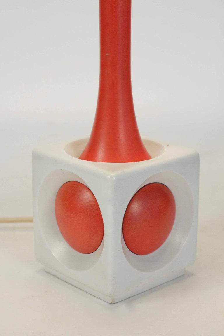 A lamp of wood painted orange and white, circa 1960, midcentury design.