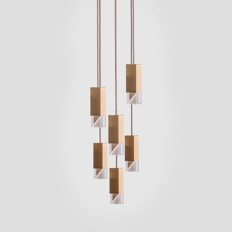 Marked by a minimal design, this exquisite chandelier of the Lamp/One Collection is a fine example of contemporary aesthetic and traditional craftsmanship. Suspended from the ceiling from a square satin brass plate (30x30cm), six fabric cables