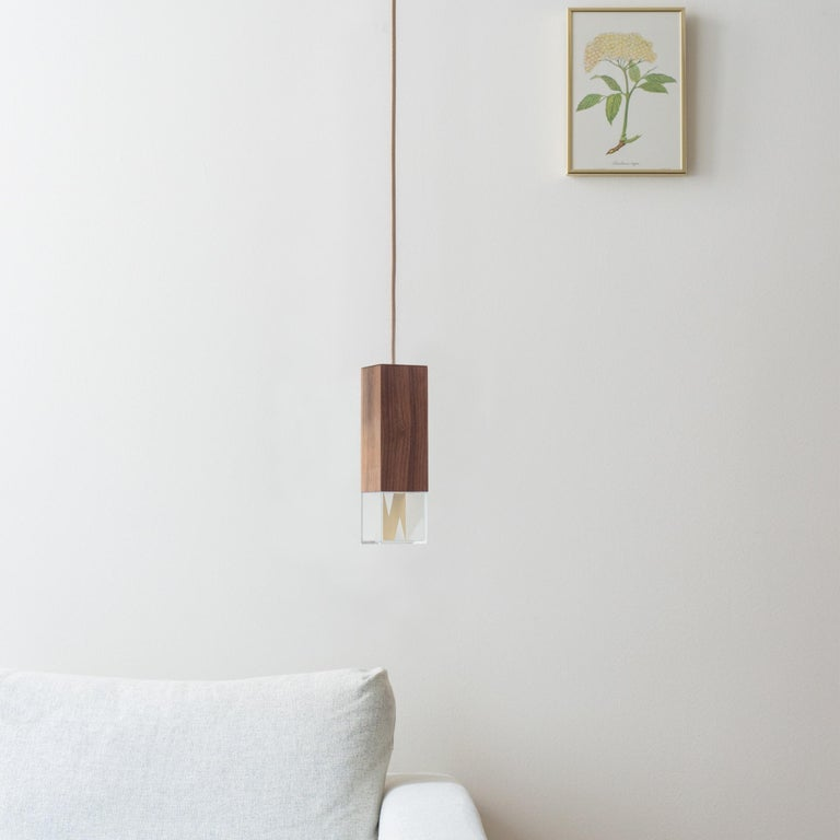 Ideal both individually and in multiples, this refined pendant lamp has a modern silhouette enriched by prized material. Entirely handcrafted of Canaletto walnut, the rectangular shade is suspended from a square ceiling plate (5x5x5cm) of solid