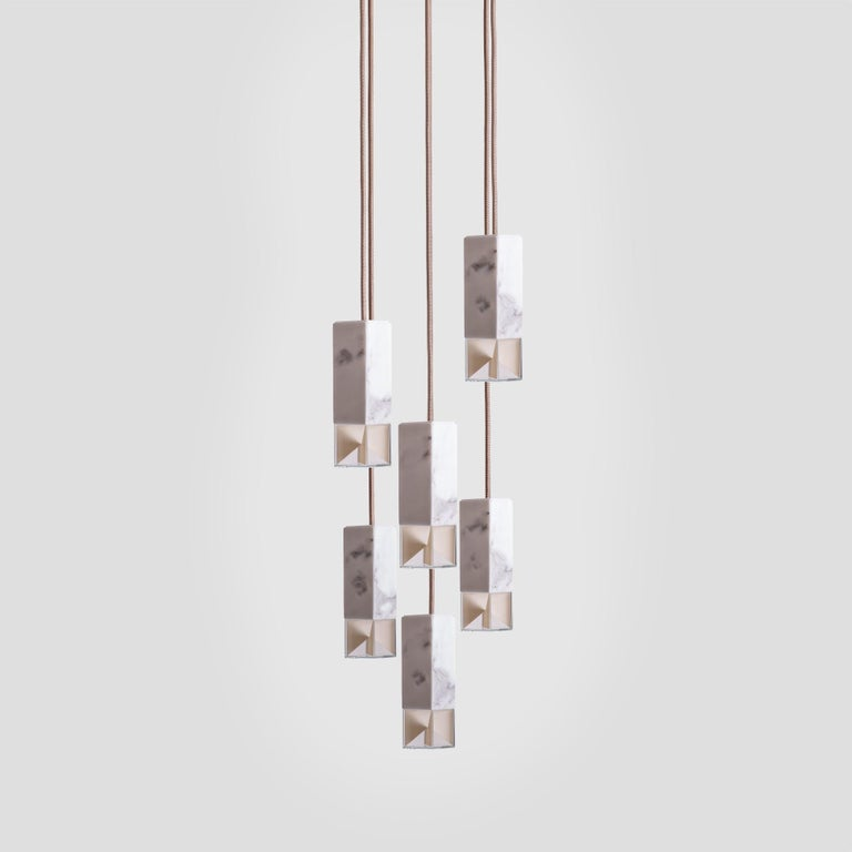 Part of the lamp or one collection, this chandelier features six rectangular shades suspended at different lengths to create a modern and alluring display. Holding each a LED G9 max 2.6W, the shades are handcrafted of white Calcutta marble with a
