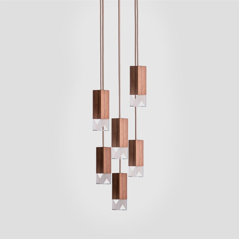 Combining a simple and elegant shape with prized materials, this modern and sophisticated chandelier features six pendants hanging from a square ceiling plate (30 x 30cm) of satin-finished brass at different lengths from adjustable fabric cables (2m